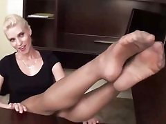 Uber-cute blond is posing on the table exposing her stocking and shoes